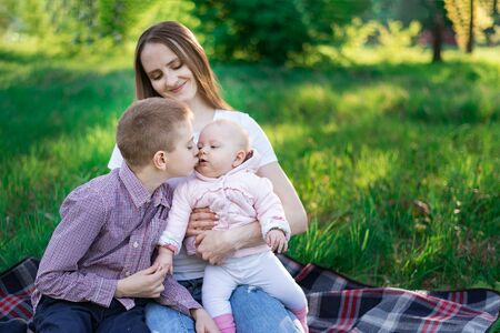 Young mother with two children in the Park. Oldest son kisses his little sister Banque d'images
