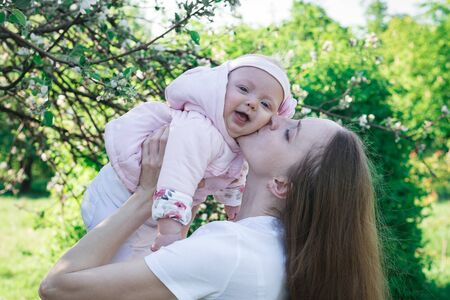 Young mother holds little laughing daughter over nature background. Child and parenthood.