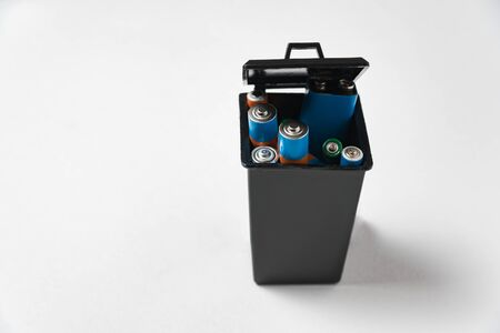 Used batteries in black garbage container on white background. Recycling batteries concept. Imagens