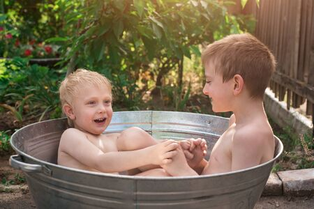 Two boys sitting in metal basin full of water and play. Children bathe in basin outside.