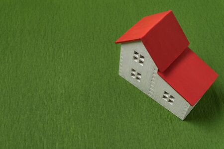 Top view on model of house on green background. Eco-friendly house concept. Mortgage Standard-Bild - 143290574