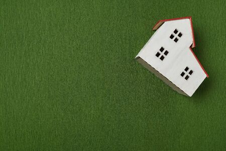 Model of house on green background. Top view. Purchase of land for construction concept. Standard-Bild - 143290600