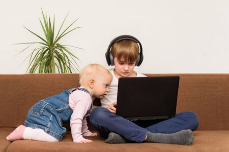 Teen boy sitting on sofa with laptop and baby girl looks curiously at the monitor. Generation Alpha concept.