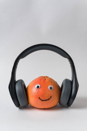 Orange smiley with headphones on white background. Fruit with eyes and smile. Food with Funny Faces