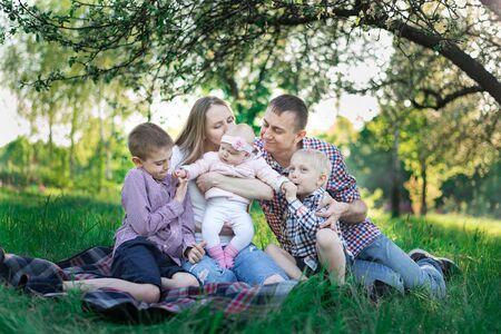 Family having picnic in countryside. Concept candid happy family and three children