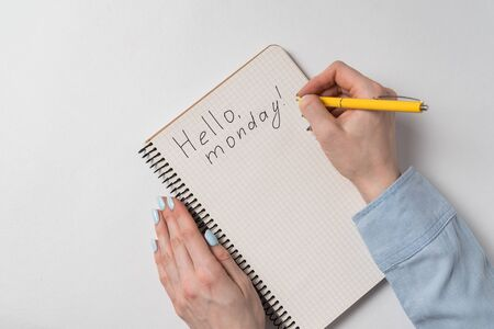 Hello monday text in copybook. Female hands writing note in Notepad. White background.