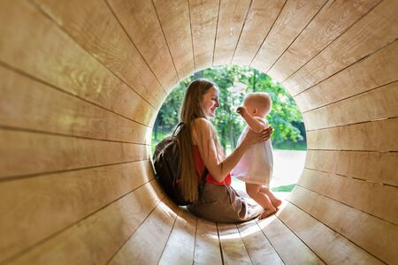 Mother playing with baby in eco-friendly playground. Wooden tunnel for children. Stok Fotoğraf