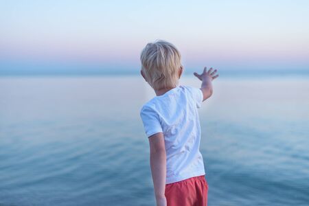 Child reaches out hand to sea. Blond boy on sea background