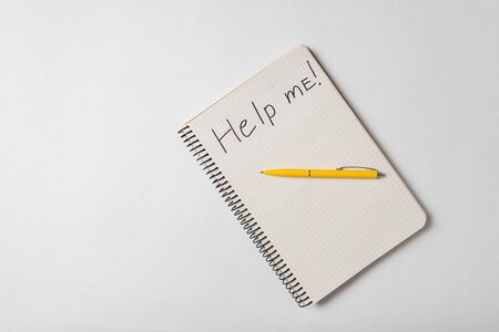 Top view of the notepad with Help Me notice on a white background. Request for assistance sos.