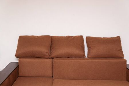 Brown corner sofa with large cushions. Upholstered furniture.
