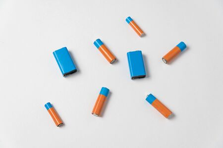 Generic AA and PP3 batteries and accumulator on a white background. Top view.