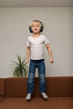 6-year-old child listens to music and jumps on couch. Vertical frame.
