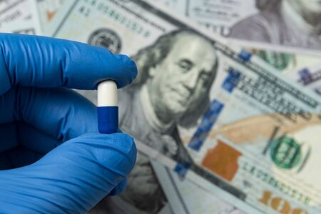 Hand in medical glove holding a pill on background of money. Cost of medicines and treatment.
