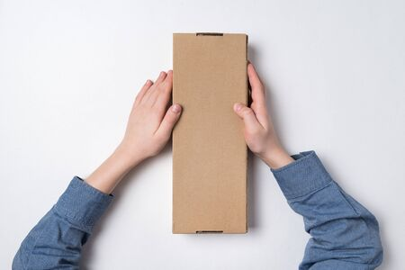 Child holds rectangular craft paper box on white background. Parcel delivery concept. Top view