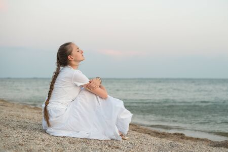 Young beautiful woman with long braid sits by the sea and dreams. Foto de archivo