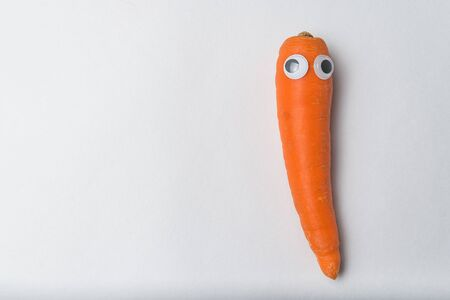 carrot with funny face and Googly eyes on white background. Vegetarianism concept.