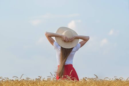 Rear view of young woman with long hair in hat in wheat field. Weekend outsides.