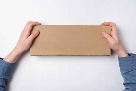 Child holds rectangular craft paper box on white background. Parcel delivery concept. Top view. Copy space