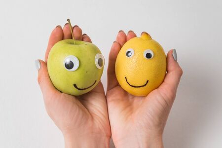 Hands holding Apple and lemon with funny faces on white background.