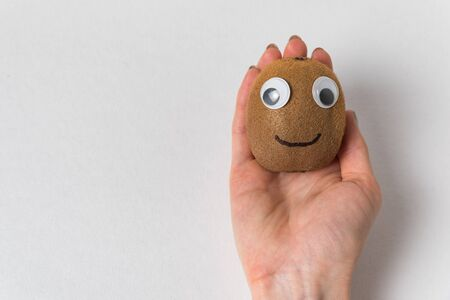 Hand holding kiwi with Googly eyes on white background. Products with funny faces.