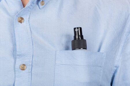 Compact spray in pocket of shirt. Antibacterial protective spray in pocket. Foto de archivo