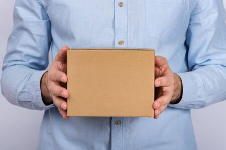 Man holding cardboard box. Delivery service. close up. copy space. mockup