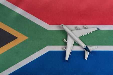 National flag of Republic of South Africa and toy airplane close up. Resumption of flights after quarantine