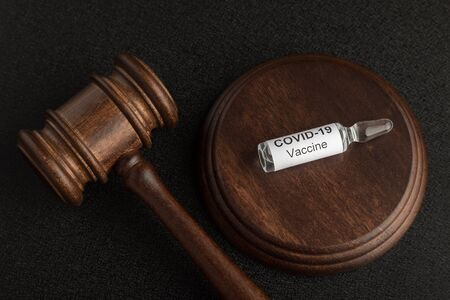 Judges gavel and glass ampoule vial with coronavirus COVID-19 vaccine. Concept laws against covid-19 Stock Photo