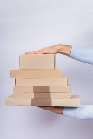 Hands holding cardboard box on white background. Delivery parcels. Vertical frame.