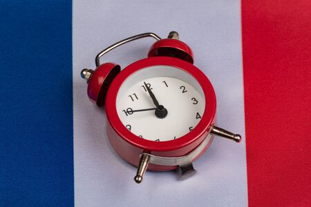 Flag of France and vintage alarm clock close up. Time to learn French.