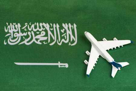 Flag of Saudi Arabia and model airplane. Opening borders after quarantine. Travels.