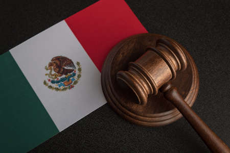 Judge or auction gavel and flag of Mexico. Mexican legislation. Violation of human rights in Mexico. Stock Photo