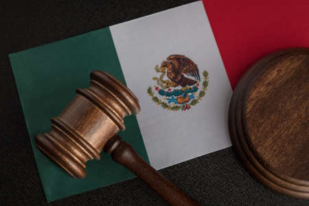 Judge or auction gavel on flag of Mexico. Mexican legislation. Violation of human rights in Mexico.
