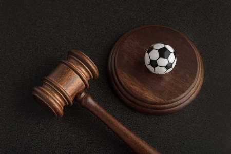 Wooden judge gavel and toy soccer ball. Football coach accused. Concussion lawsuit Foto de archivo