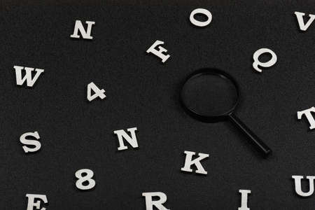 White English letters and numbers and magnifying glass on black background. Search concept. Stock fotó