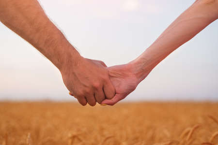 Young couple holds each other's hands. Field of ripe wheat and the sky on background. Stock fotó