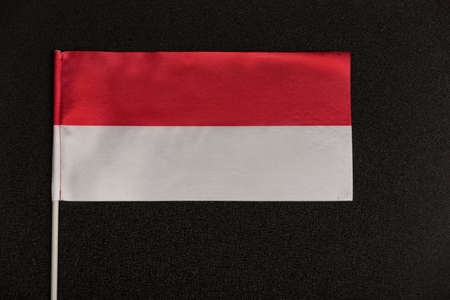 Table flag of Poland on a black background. Red-white flag