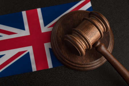 Judge Gavel and flag of United Kingdom. Law and justice in UK. Violation of rights and freedoms in Britain.