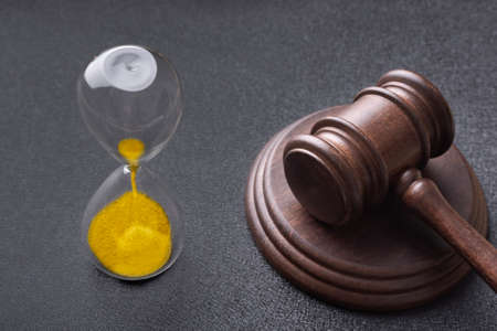 Hourglass and judges gavel on black background. Law and time.