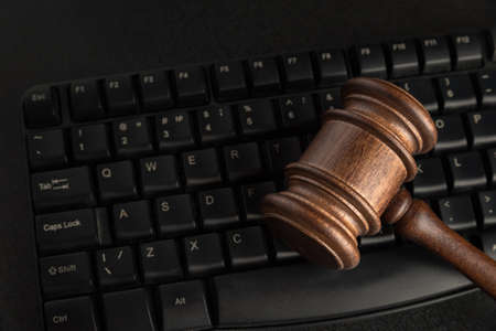 Wooden Judges gavel and keyboard. Close up. Legal rights to use the names of mail and websites.