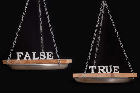Words truth and false on scales. Disbalance. Black background close up.