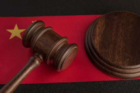 Judge gavel near the China flag. Law and legality concept. Violation of human rights.