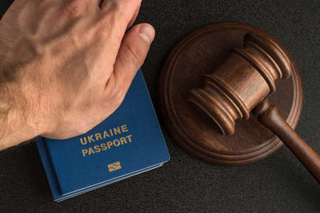 Male hand holds a Ukraine passport next to the judge's gavel. Obtain citizenship 版權商用圖片