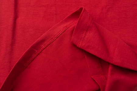 Red cotton fabric close up. hem tee shirts, dress hem. fabric stitching.