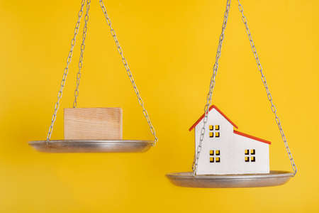 Balance scales and model home on yellow background close up. Choice concept