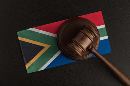 Judges hammer and flag of South Africa. Law of South Africa. Violation of rights.