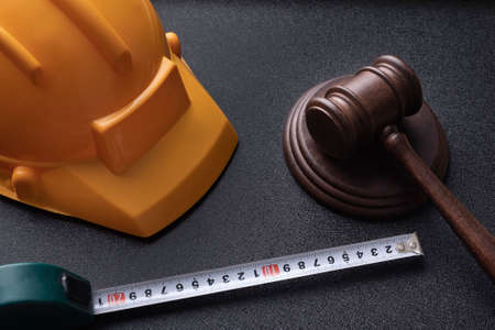 Wooden judge gavel, yellow building helmet and tape. Construction law concept. labor-related legal concept.