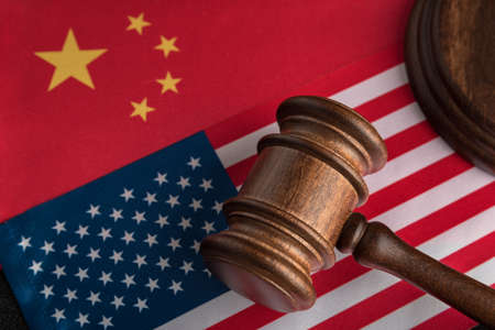 Judge gavel on the flag of the US and China. Trade war between China and the United States. Legal fight.