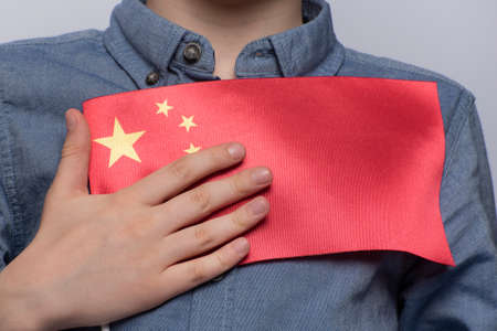 Child holds flag of China. Close up. Education in China. Study of Chinese language