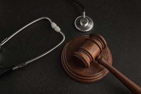 Gavel hammer of judge and stethoscop on black background. Sentence on medical negligence